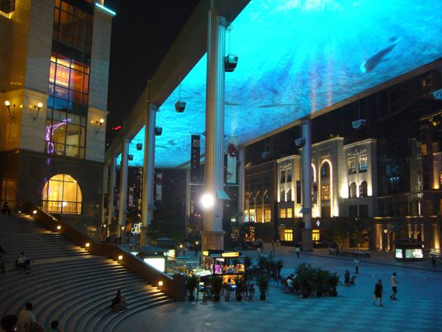 """V dokončovaném nákupní centru The Place v čínském Pekingu se před časem odehrála veliká show. Slavnostně spustili gigantickou, 250 metrů dlouhou a 30 metrů širokou, obrazovku. Její název je """"Sky Screen"""" a tvoří ji složené diody LED. Obrazovka je zavěšena ve výšce 25 metrů nad náměstím. Díky mřížové struktuře umístění skrz tento """"strop"""" bez problémů proniká denní světlo."""