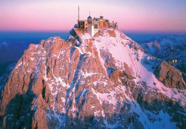 """Od prvního zaseknutí krumpáče při stavbě """"železnice snů"""", vedoucí až pod vrchol nejvyšší německé hory v v Bavorských Alpách Zugspitze (2964 m), uplynulo právě letos 80 let. První myšlenky na pokoření Zugspitze lidskou technikou jsou dokonce přesně 100 let staré. Radní Garmisch-Partenkirchenu totiž požádali Královské bavorské ministerstvo o vypracování plánů na zpřístupnění Zugspitze lanovkou už v roce 1908!"""