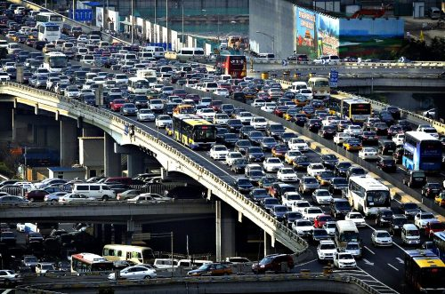 Lines of cars are pictured during a rush hour traffic jam on Guomao Bridge in Beijing...Lines of cars are pictured during a rush hour traffic jam on Guomao Bridge in Beijing July 11, 2013. Eight more cities in China, the world's biggest auto market, are likely to announce policies restricting new vehicle purchases, an official at the automakers association said, as Beijing tries to control air pollution. REUTERS/Jason Lee (CHINA - Tags: TRANSPORT ENVIRONMENT BUSINESS TPX IMAGES OF THE DAY)